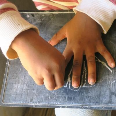 A child outlines her hand with chalk during a skills development lesson with a volunteer working with children in Madagascar.